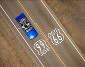 Route 66'da yolculuk yapan Ford Mustang Cabrio ve mutlu bir çift.  Sanatçı: Raf Willems