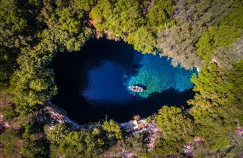 Yunan adası Cephalonia'daki Melissani mağarasını tekne ile keşif. Sanatçı: Calin Stan